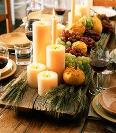 Arrange a large group of scentless white pillar candles in various heights on a large wooden tray in the center of your dining table. Add wheat stalks, fresh fruit, and gourds for an extra festive display.