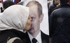 In this March 4, 2012 file photo, a Syrian woman kisses a poster of Russian President Vladimir Putin during a pro-Syrian government protest in front of the Russian Embassy in Damascus, Syria.