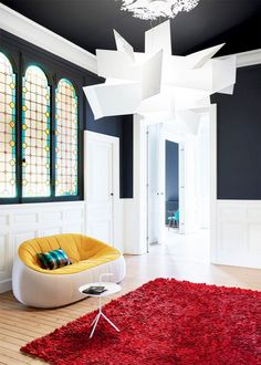 Ultra-modern living space with original stain glass windows, a chandelier, and a mod yellow sofa