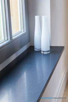 Een mooie natuursteen vensterbank met een donkergrijze kleur en een zoete afwerking. deze vensterbank kan op maat gemaakt worden.