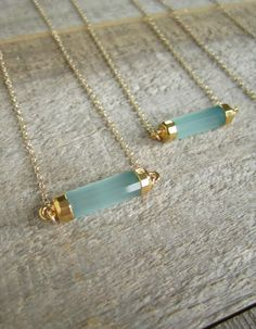 Serene sea green chalcedony cylinder rests sideways on a 14K gold filled cable chain.