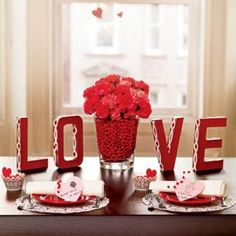 Cut letters from styrofoam, paint them in red and trim them with a ribbon. Place a rich bouquet of flowers in the centre, arrange letters and match colour of napkins to the red in letters and flowers~mama-knows.com