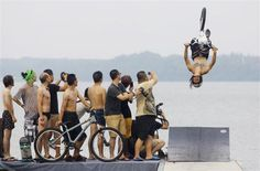 Observers take pictures as an extreme cycling enthusiast performs a stunt with a bicycle during a diving activity at the East Lake in Wuhan, Hubei province July 9, 2012. This activity, which is held by local netizens, attracts many extreme cycling enthusiasts to take part, local media reported. Picture   REUTERS/China Daily