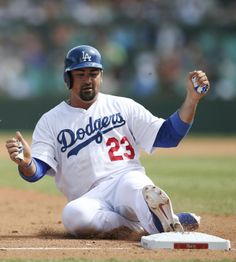 The Los Angeles Dodgers' Adrian Gonzalez slides into third base during the second game of the two-game Major League Baseball opening series between the Los Angeles Dodgers and the Arizona Diamondbacks at the Sydney Cricket Ground in Sydney, Sunday, March 23, 2014. (AP Photo/Rick Rycroft)