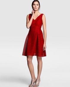 Vestido corto, en color rojo, con detalle de rayas caladas horizontales. Sin mangas, escote de pico y corte a la cintura con falda con pliegues.