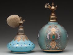 "VICTORIAN DECORATED ATOMIZERS, colorless cased blue and opaque blue, each with polychrome enamel and gilt decoration, original gilt-metal mounts. Late 19th/early 20th century. 5 3/4"" and 4"" $75 - $125"