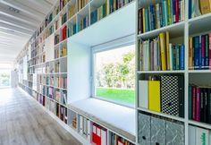 La parete disegnata a libreria dallo studio Foldes Architecst nella casa di campagna in Ungheria si interrompe creando una finestra con nicchia imbottita, dove accovacciarsi per leggere. Oltre la vetrata uno scorcio verde