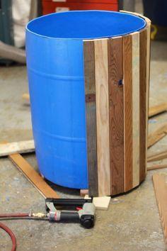 Reclaimed wood transforms a blue barrel (or ugly plastic pot) into a beautiful planter. (habiller le récupérateur eau pluie)