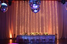 Fondo de mesa principal con tiras de mini luces de 6 metros de altura. Sobre la mesa, camino con flores blancas y mucho follaje, Sillas Tiffany doradas by Mercedes Courreges Ambientaciones