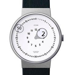 Reloj de muñeca donde las manecillas acaban en una pequeña lente que aumenta el número de la hora, en un círculo inferior, y el minuto, en un círculo exterior.