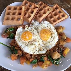 """Paleo waffles served with free range eggs on top of a hash made with sweet potatoes, yellow bell pepper, cauliflower rice, apples, onion, fennel and spinach.   #paleobreakfast #paleohash #paleowaffles #freerangeeggs"" Photo taken by @paleohope on Instagram,"