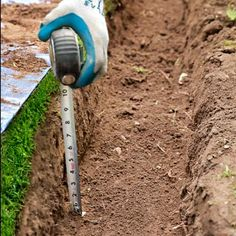 Dig until the soil changes color, indicating that you've gotten past the topsoil. Measure the depth of your trench, as shown; it should be at least 6 inches deep to allow for a 2- to 3-inch layer of paver base, 1 inch of stone dust, and the bricks set flush with the ground.
