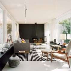 Sala de estar com paredes de vidro e uma lareira super moderna.