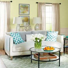 Use decor to refine your room's palette. Neutral curtains and table lamps coordinate with a woven, patterned rug. Pillows featuring bursts of blue tie in a bold accent color. Fruit, flowers, and accessories provide avenues for fine-tuning your color scheme with pops of color and crisp whites.