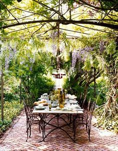 Outdoor Dining from House Beautiful- wisteria arbor, iron work or arbor, brick patio (love color & texture)