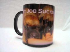 """Color change coffee mug with 5 puppies sucking on fingers with the caption """"My Job Sucks"""". This unique mug is a dark when cool, add a warm drink into it and watch as the dark color vanishes and the puppies sucking on the end of the fingers emerges before your eyes. When the ceramic cools down again the mug turns the dark color until refilled wit..."""
