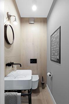 W toalecie równie udany melanż tworzy minimalistyczne, industrialne wyposażenie (grzejnik, bateria, kinkiet) na tle drewnianej ściany.