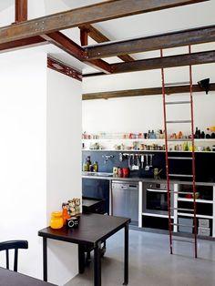 cuisine avec un comptoir le long d\\'un mur et devant la table de repas