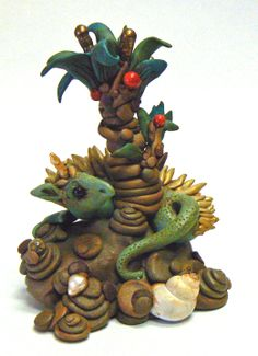 """SOLD  """"Percival in the Garden of Delights"""" Well, he doesn't know exactly how he got in the garden, but one thing's for sure - this tree is probably delicious, so he'll just guard it and make sure no one else gets to that juicy red fruit. This sculpture stands about 4 inches tall and almost as wide, embellished with black onys, pearl, ocean jasper, shell, coral."""