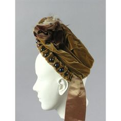 1885 Bonnet Culture: American Medium: velvet, cotton, wire, glass, silk woman's bonnet of a golden-brown-colored silk velvet decorated with glass beads, feathers, and ribbons. The hat, shaped to perch on the back of the wearer's head, has a brim that angles up and away from the bottom of the crown and the wearer's face.