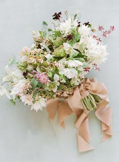 The bride's bouquet by Heirloom Design House included hellebores, ranunculus, orchids, astrantia, and blushing-bride protea, all tied with a hand-dyed silk ribbon from Froufrou Chic.