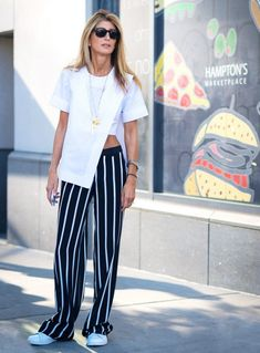 An asymmetrical white top is paired with striped pants, layered necklaces and sneakers.