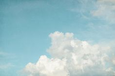 Fluffy white clouds in a blue summer sky evoke memories of childhood... sitting in the grass finding shapes in the sky