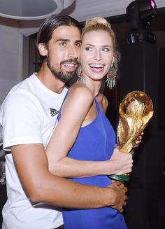 While blond beauty Lena Gercke held on to boyfriend Sami Khedira's World Cup trophy, the soccer player held on to her following Germany's World Cup championship.