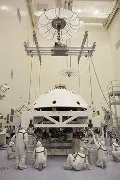 In the Payload Hazardous Servicing Facility at NASA's Kennedy Space Center in Florida, technicians guide the backshell as it is lowered over NASA's Mars Science Laboratory (MSL) rover, Curiosity, for encapsulation.