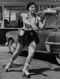 A car hop on roller skates skillfully delivers a tray full of food to  customers.