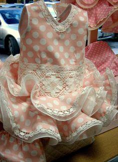 Traje de flamenca bebé ,confeccionado en popelín rosa con lunar blanco, doble volante de organdi; bolillo en orilla y cuerpo.