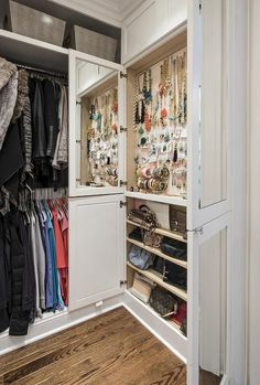 Fantastic walk-in closet features floor to ceiling built-ins filled with gray baskets stacked over clothes rails.
