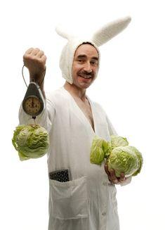 Mann im Hasenkostüm wiegt Salat.