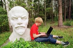 Lina Mackonyte takes a break from sightseeing in Gruto Park to write emails to friends beside a statue of Soviet Union founder Vladimir Lenin in Druskininkai, Lithuania, on August 9, 2001.