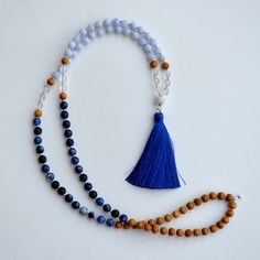 The Holistic Rain Blue Lotus Mala. In traditional Buddhist culture, tassels are symbolic of the roots of lotus blossoms growing down into the earth, grounding us and connecting us as one. Lotus blossoms promote enlightenment, and represent spiritual power, and purity of mind, body, and speech. Handmade. #Malabeads #Tassel