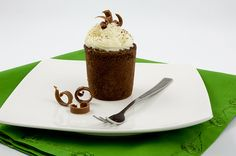 A photo of a chocolate genoise & white chocolate mousse cake on a white dish with a silver fork and 3 chocolate curls placed on a green napk...