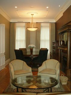 Decorative floor to ceiling beige curtains with functional privacy white curtains.  Interesting to see white crown molding up against dark curtain rods...not sure I love that combo, but also not sure what else could be done.  (Lower the rods to just above the window?)