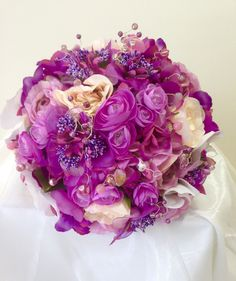 The spec for this brides silk posy was lilac and lots of it with a touch of cream.  We used roses and ranunculus with lots of crystal and organza detail. www.am-flowers.co.uk