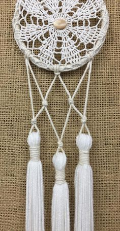 Small, white & neutral tone, crocheted, lace doily dreamcatcher made with unbleached, hand-knotted cotton, salvaged materials and decorated with mother of pearl and tassels. hoop: 4 length from top of hoop: 21 This item is one of a kind, made by hand & assembled with natural & found