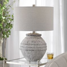 MONTSANT TABLE LAMP Showcasing an old world style, this ceramic table lamp has a heavily distressed stone ivory finish and aged gray undertones, accented with brushed nickel plated details. The hardback drum shade is an off-white linen fabric. Living Room Seating, Living Room Chairs, Living Room Lighting Design, Cube Table, Driftwood Table, Wooden Side Table, Rustic Table, Old World Style, Ceramic Table Lamps