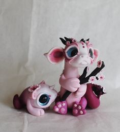 This is a cherry blossom themed dragon we made for a custom order. Next to it is something we made from it's leftover body-bits. (Let's ignore how disturbing that sounds, shall we?) We're not sure what the little guy is, but we think he's adorable....