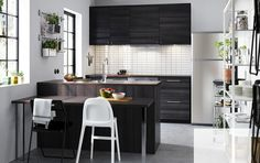 A small kitchen with black wood effect drawers, doors and open storage with space for plates, glasses and bowls.