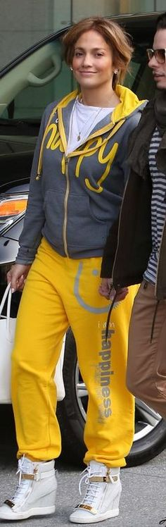 Who made  Jennifer Lopez's gray sweatshirt, yellow print pants, gold plate wedge sneakers, and white tote handbag that she wore on January 9, 2013?