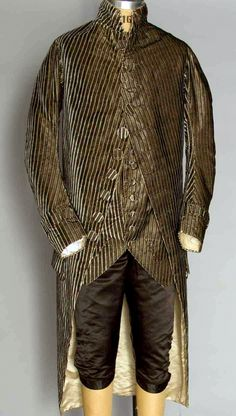 "Gentleman's three piece suit (frockcoat, waistcoat, breeches), 1775-1780. Coat & waistcoat of cut & uncut velvet, narrow blue & cream stripes alternate w/ stripe of tiny windowpane grid in black velvet cut to beige silk, 2"" stand coat collar, round, flat self-fabric buttons, black satin knee breeches"