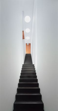 This single-flight stair way, which is lit from above, connects all three levels…