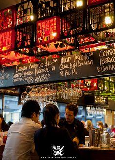 "Bar tapas ""movida"" en Melbourne. Pizarra cajas bebida pantallas luz"