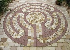 In 2007 The Labyrinth Builders were awarded a silver medal for 'The Labyrinth Garden' at the RHS Hampton Court Palace Flower Show. By word of mouth our client heard of and saw images of the garden and commissioned The Labyrinth Builders to recreate the labyrinth in her own garden so providing the perfect permanent setting for this beautiful natural stone labyrinth.    Formed by bespoke 'tumbled' sandstone paviors the labyrinth is small (diameter 2.9m) but  still fully 'walkable'.