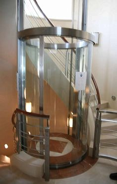 Elevator in home? Maybe it will keep me from falling down the stairs : ) Doug: Stairs wrapped around a glass elevator. Cool and practical...