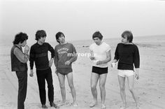 "The Rolling Stones. Bill Wyman, Mick Jagger, Keith Richards, Charlie Watts and Brian Jones seen here posing on Malibu beach. According to the photographers "" The boys had some hamburgers and played football and were happy to be beside the sea"" However it was too cold to go swimming. During the band's first US tour, 4th June 1964"