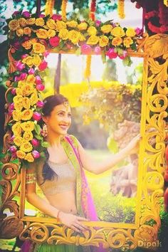 photo op with a colourful yellow photo frame with flowers and.a pretty Indian bride looking through | Indian wedding photoshoot ideas | Dipak Studios | The ultimate guide for the Indian Bride to plan her dream wedding. Witty Vows shares things no one tells brides, covers real weddings, ideas, inspirations, design trends and the right vendors, candid photographers etc.| #bridsmaids #inspiration #IndianWedding | Curated by #WittyVows - Things no one tells Brides | www.wittyvows.com
